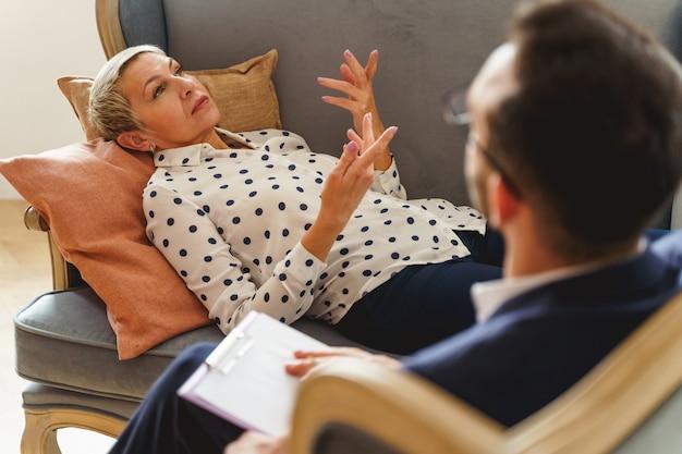 Uważna, zrelaksowana, stylowa, starsza pacjentka rasy kaukaskiej leżąca na kanapie w swoim gabinecie psychoanalityka