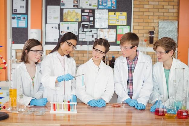 Uważne dzieci w wieku szkolnym przeprowadzają eksperyment chemiczny w laboratorium