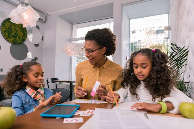 Uważne słuchanie. kręcone, ciemnowłose słodkie dziewczyny uważnie słuchają nauczyciela opowiadającego im o listach