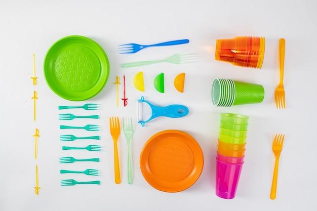 Uważne używanie. jasne talerze i widelce leżące z szaszłykami i kubkami z taniego, niebezpiecznego plastiku
