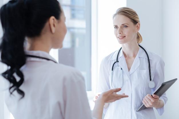 Uważni i przyjaźni komunikatywni lekarze pracujący w szpitalu i cieszący się rozmową trzymając cyfrowy gadżet
