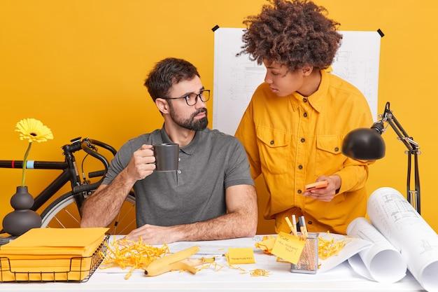 Uważni współpracownicy uważnie patrzą na siebie, sprawiają, że szkice konstrukcji budynku są bardzo pracowite, sprawiają, że raport pozuje w przestrzeni coworkingowej, robi bałagan na biurku. koncepcja inżynierska