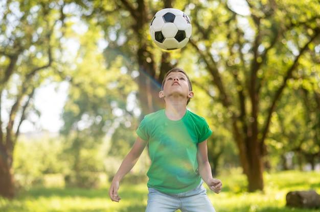 Uważny chłopiec patrzący na piłkę nożną w powietrzu