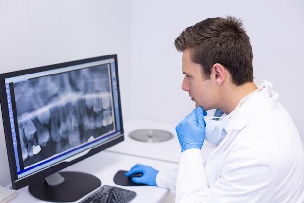 Uważny dentysta bada raport rentgenowski na komputerze