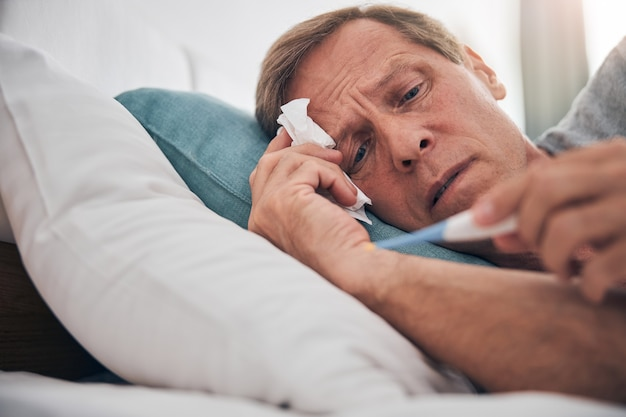 Uważny dojrzały mężczyzna marszczący czoło podczas pomiaru temperatury, leżący w swoim łóżku