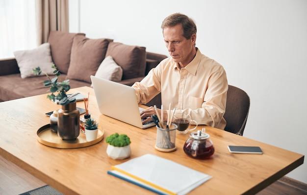 Uważny dojrzały mężczyzna siedzący w swoim miejscu pracy i piszący wiadomość online w salonie