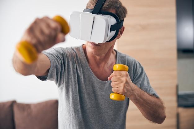 Uważny dorosły mężczyzna noszący maskę vr podczas treningu online w domu