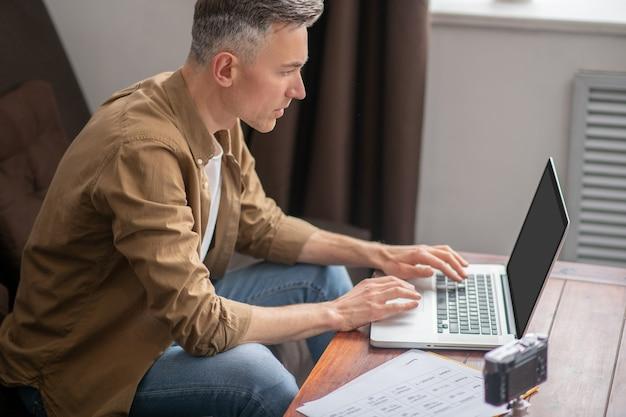 Uważny mężczyzna patrzący na laptopa z zainteresowaniem