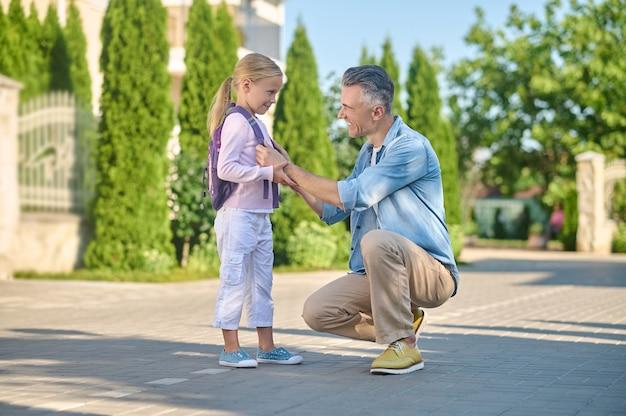 Uważny mężczyzna przyczajony obok swojej córeczki