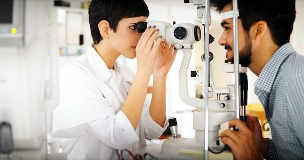Uważny optometrysta badający pacjentkę na lampie szczelinowej w klinice okulistycznej