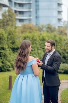 Uważny, skoncentrowany atrakcyjny mężczyzna proponuje i długowłosy kobieta z powrotem do aparatu stojącego na ulicy