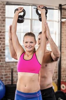 Uważny trener mięśni pokazać, jak podnosić kettlebells