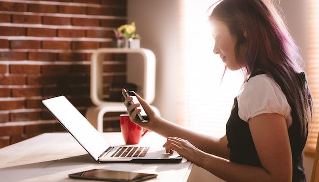 Uważny wykonawca za pomocą laptopa i telefonu komórkowego