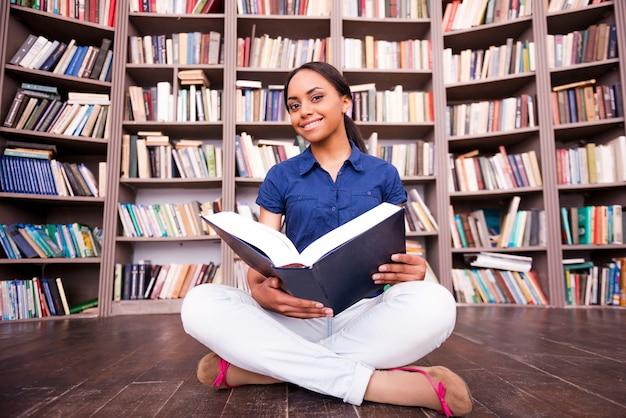 Uwielbia czytać. piękna afrykańska studentka trzymająca książkę i uśmiechająca się do kamery siedząc na podłodze w bibliotece