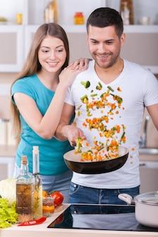 Uwielbiają razem gotować. piękna młoda para wspólnie gotuje w kuchni