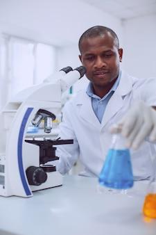 Uwielbiam bioinżynierię. inteligentny, doświadczony biolog pracujący ze swoim mikroskopem i trzymający probówkę