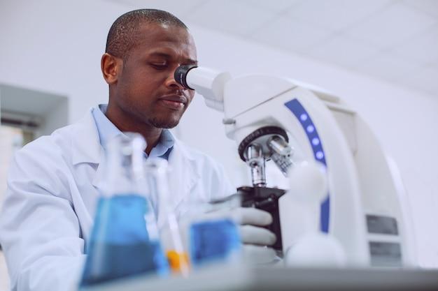 Uwielbiam biologię. skoncentrowany zawodowy biolog pracujący ze swoim mikroskopem i ubrany w mundur