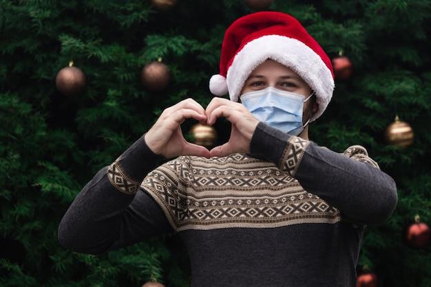 Uwielbiam boże narodzenie. ścieśniać portret mężczyzny w kapeluszu świętego mikołaja, swetrze xmas i masce medycznej z emocjami. na tle choinki. koronawirus pandemia