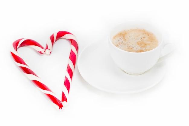 Uwielbiam kawę, serce z cukierków z filiżanką kawy na białym tle.