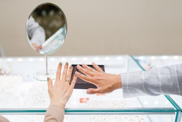 Uwielbiam kilka rąk z obrączkami, sklep jubilerski. mężczyzna i kobieta wybierając złotą dekorację. przyszła panna młoda i pan młody w sklepie jubilerskim