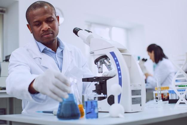 Uwielbiam naukę. poważny zawodowy biolog pracujący ze swoim mikroskopem i współpracownikiem pracującym w tle