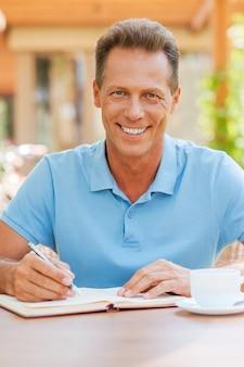 Uwielbiam pracować na świeżym powietrzu. pewny siebie, dojrzały mężczyzna piszący coś w notesie i uśmiechający się siedząc przy stole na zewnątrz z domem w tle