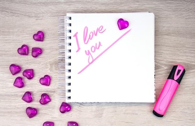 Uwielbiam różowy list, walentynkową kartkę, notatnik z napisem kocham cię i długopis leżący na białym tle. walentynki. list miłosny. pisanie markerem