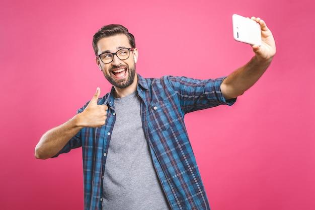 Uwielbiam selfie! przystojny młody mężczyzna w koszuli trzymając aparat i robiąc selfie i uśmiechając się. słuchanie muzyki przez słuchawki.