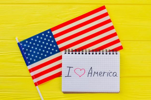 Uwielbiam stany zjednoczone ameryki. amerykańska flaga i notatnik na żółtym drewnie.