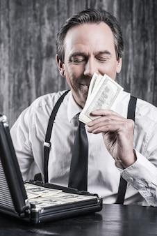 Uwielbiam zapach pieniędzy. zadowolony starszy mężczyzna w koszuli i szelkach siedzi przy stole i wącha pieniądze, podczas gdy obok niego leży walizka pełna papierowej waluty