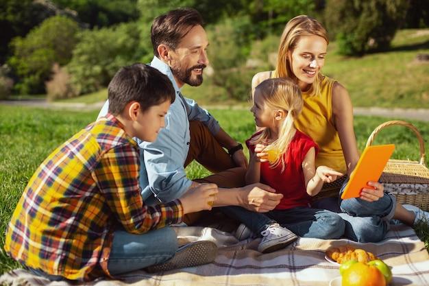 Uwielbiamy pikniki. zachwycona blond matka trzymająca tablet podczas pikniku z rodziną