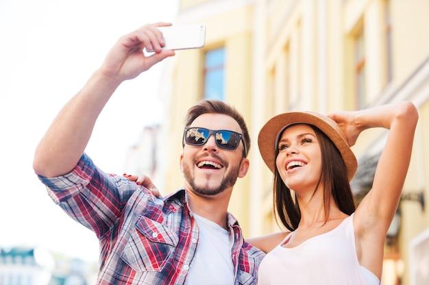 Uwielbiamy robić selfie. niski kąt widzenia szczęśliwej młodej kochającej się pary robi selfie stojąc razem na zewnątrz