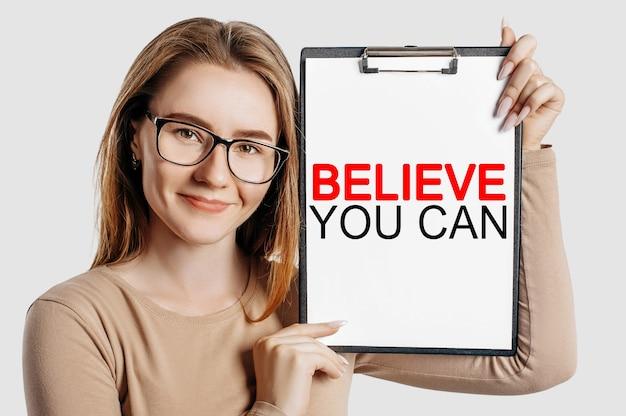 Uwierz, że możesz. piękna młoda biznesowa kobieta w okularach trzyma schowek z miejsca na białym tle na szarym tle