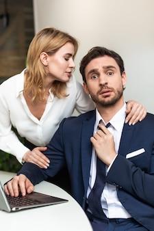 Uwodzenie w koncepcji biura. ładna kobieta dotykając kolegę, który siedzi przy stole patrząc na