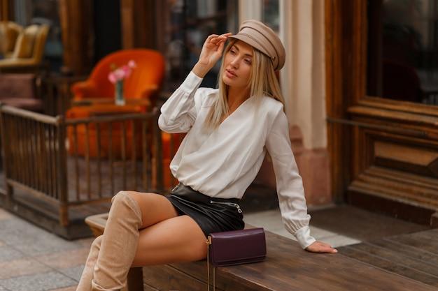 Uwodzicielska blond kobieta siedzi na ławce z idealnymi nogami