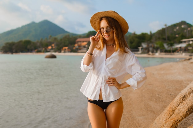 Uwodzicielska blond kobieta w białej bluzce pozuje na tropikalnej plaży