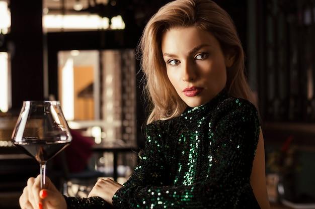 Uwodzicielska blondynka w zielonej sukni wieczorowej pozuje przy lampce czerwonego wina.