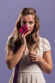 Uwodzicielska kobieta pozuje podczas gdy trzymający kwiatu