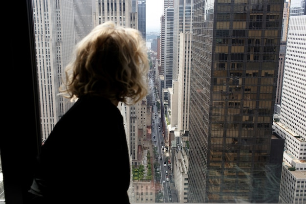 Uwodzicielska kobieta w czarnej jedwabnej szacie siedzi na parapecie patrząc na nowy jork