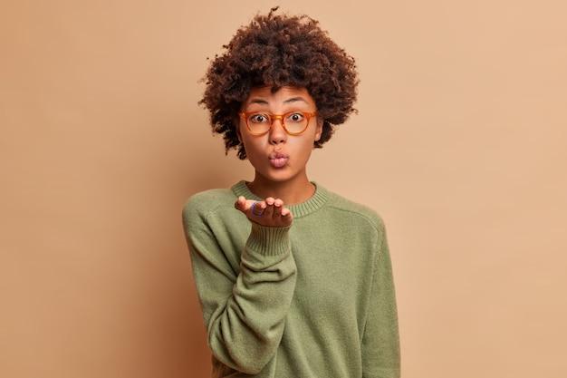Uwodzicielska ładna dziewczyna z włosami afro wysyła mwah z przodu sprawia, że gest pocałunku w powietrzu flirtuje z tobą, ma złożone usta, wyraża podziw, wygląda czule ubrana, swobodnie pozuje w domu