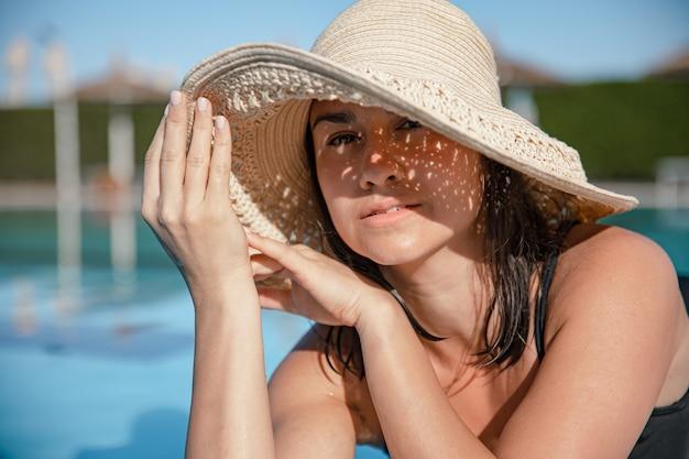 Uwodzicielska młoda kobieta relaks w słońcu przy basenie w słomkowym kapeluszu w słoneczny dzień. koncepcja kurort i lato.
