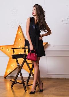 Uwodzicielska modna kobieta w eleganckiej czarnej sukience i niesamowitej biżuterii pozuje