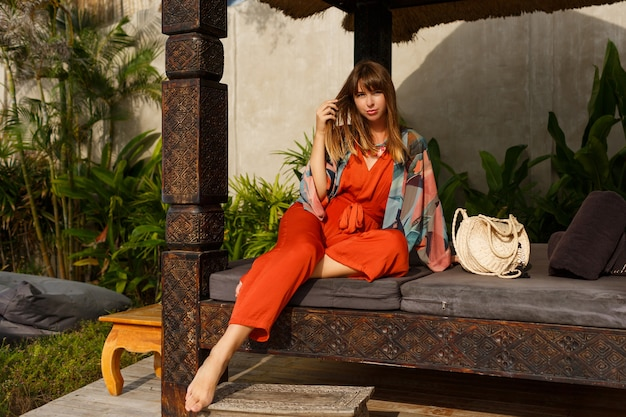 Uwodzicielska stylowa kobieta w cygańskich letnich ubraniach pozuje w tropikalnym luksusowym kurorcie. koncepcja wakacji.