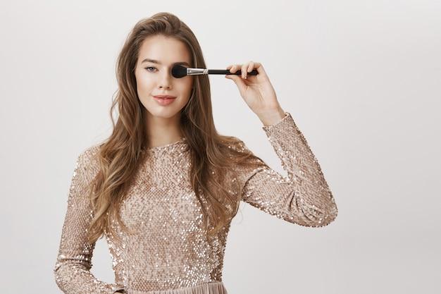 Uwodzicielska uśmiechnięta kobieta w stroju wieczorowym, zakryj oko pędzlem do makijażu