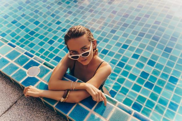 Uwodzicielska wdzięku kobieta w stylowych żółtych kolczykach z idealnym ciałem pozuje w basenie podczas wakacji w luksusowym kurorcie