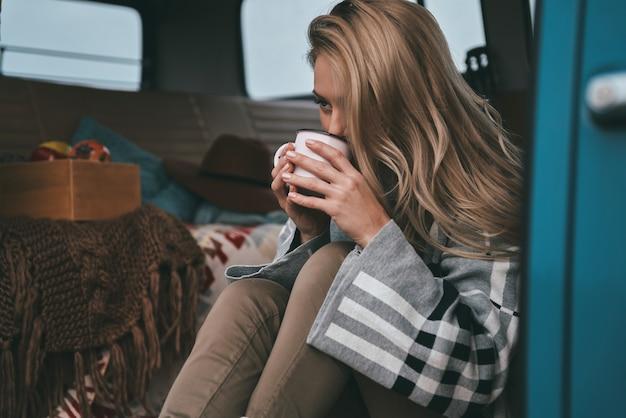 Uwolnij głowę. atrakcyjna młoda kobieta pijąca z kubka i odwracająca wzrok, siedząc wewnątrz niebieskiego mini vana w stylu retro