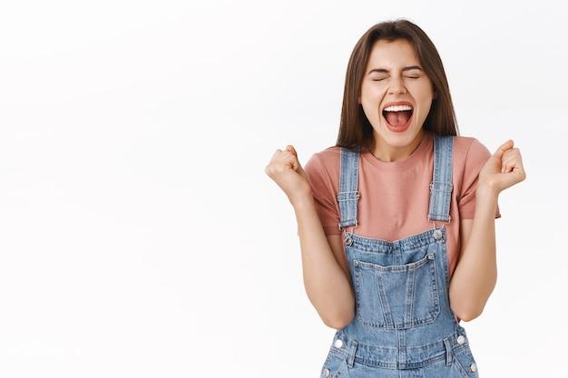 Uwolniona i szczęśliwa atrakcyjna kobieta radująca się, krzycząca tak radośnie zaciskająca pięści, osiągająca sukces, zostać mistrzem lub zwycięzcą, zamykająca oczy triumfujące, wygrywająca na loterii, białe tło