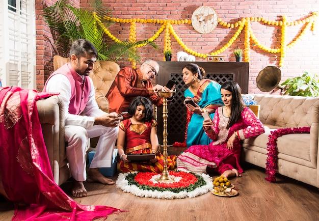 Uzależnienie od cel phone w indiach - wielopokoleniowa indyjska rodzina korzystająca ze smartfona na festiwalu diwali z domem udekorowanym diyą diwali, kwiatami rangoli i słodyczami do jedzenia