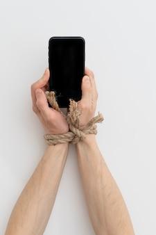 Uzależnienie od internetu lub mediów społecznościowych, ręce związane liną trzymają smartfon