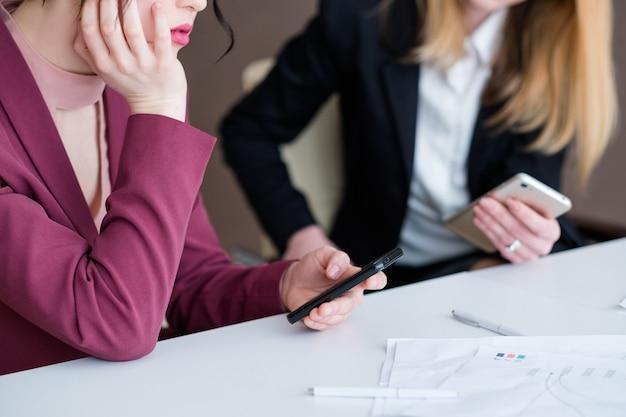 Uzależnienie od technologii. kobiety biznesu przy użyciu swoich telefonów na spotkaniu w biurze.